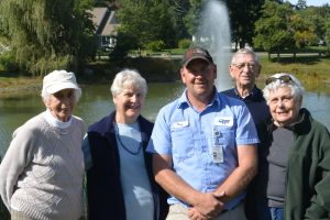 Doug Gilson (center) poses at the pond with a few of the many residents who took part in the trout-stocking initiative. From left: Skip Gambell, Ann Bex, Phil Dufour, and Mary Carlson.